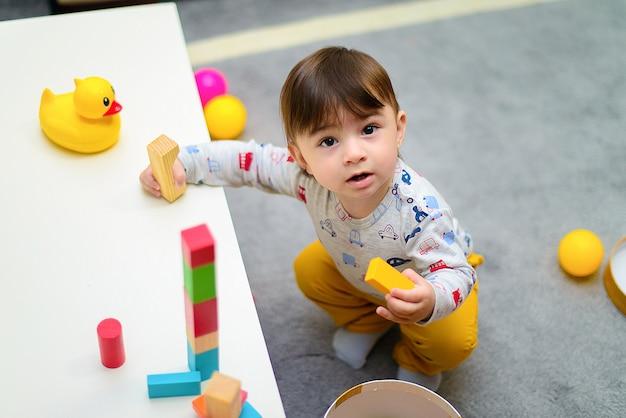 Lindo niño disfrutando mientras jugaba con juguetes o bloques en su habitación