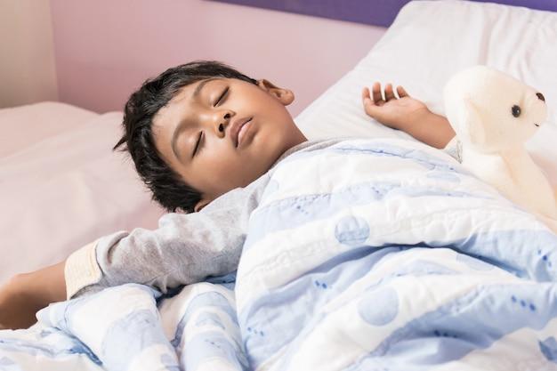 Lindo niño duerme en la cama en la habitación