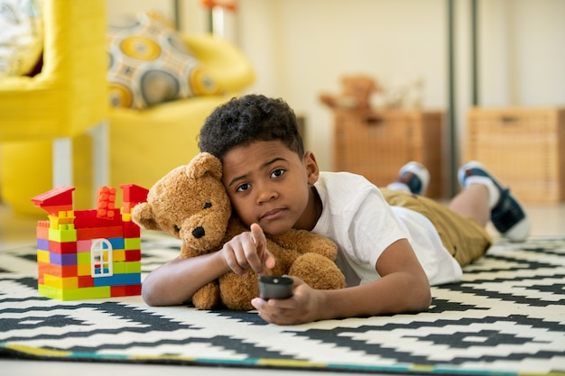 Lindo niño en edad preescolar africano con control remoto y osito de peluche marrón apuntando hacia usted mientras está acostado en el piso de la sala de estar