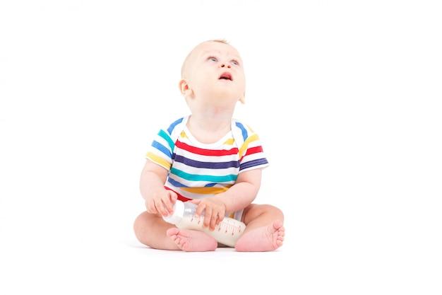 Lindo niño feliz en camisa colorida con leche