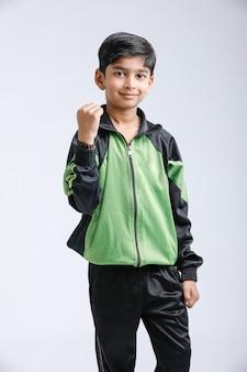 Lindo niño indio jugando y dando expresión múltiple