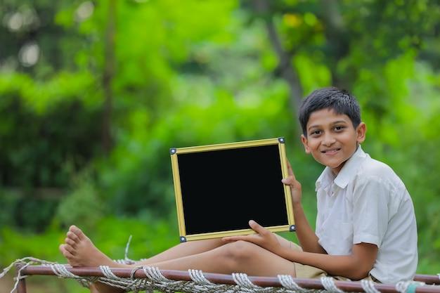 Lindo niño indio mostrando pizarra con espacio de copia
