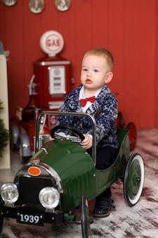 Lindo niño está jugando con autos de juguete, monta un avión de máquina de escribir de juguete, infancia feliz
