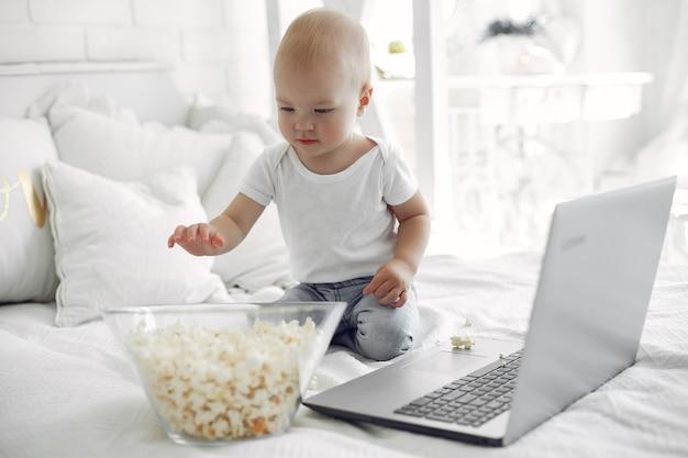 Lindo niño jugando con una computadora portátil en una cama