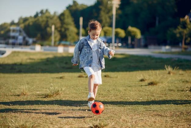 Lindo niño jugando en un parque de verano