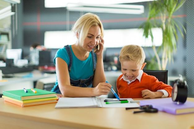 Lindo niño y mujer se sientan en el escritorio de la oficina
