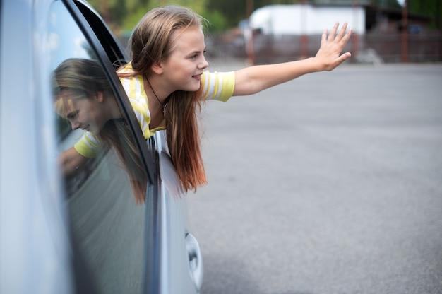 Lindo niño niña adolescente sonriendo y divirtiéndose para viajar en coche y mirando desde la ventana del coche en la ciudad