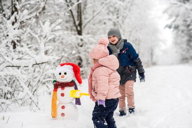 Lindo niño y niña construyendo muñeco de nieve en bosque blanco de invierno