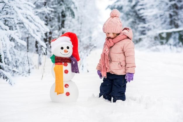 Lindo niño y niña construyendo muñeco de nieve en bosque de invierno blanco