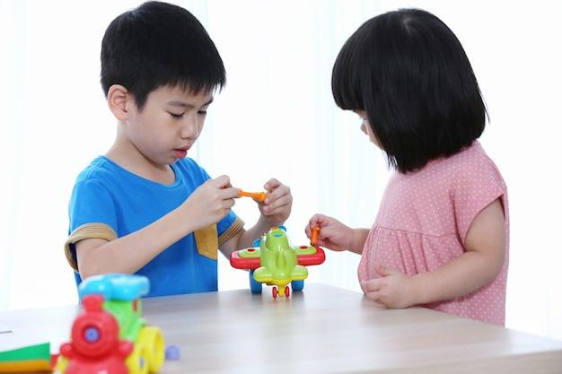 Lindo niño y niña está jugando herramientas de servicio con avión de juguete. un niño que trabaja con herramientas de juguete. un pequeño artesano.