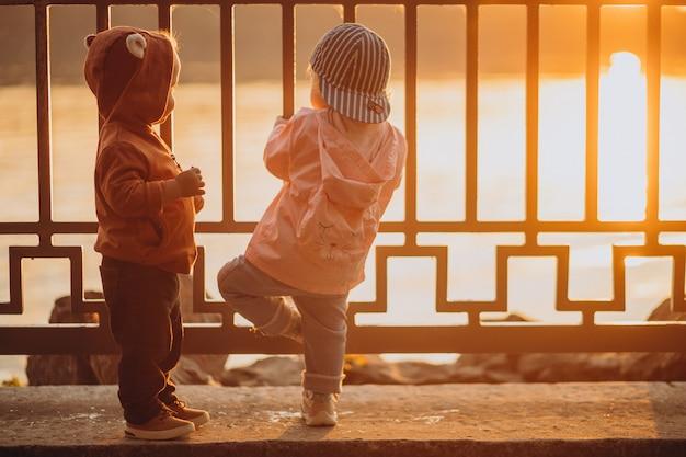 Lindo niño y niña juntos en el parque otoñal