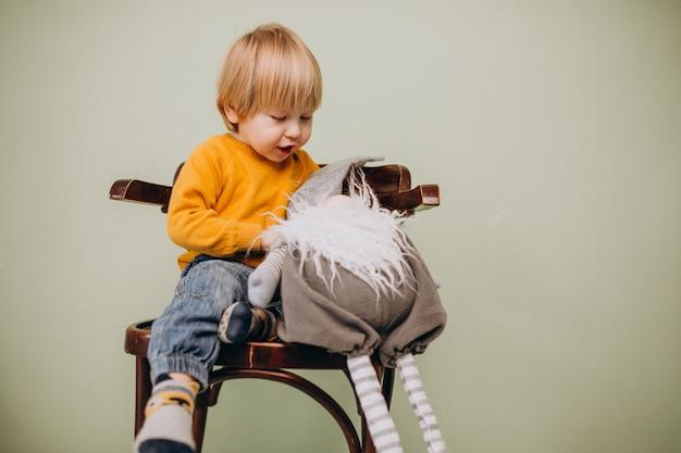 Lindo niño pelirrojo sentado en una silla con juguete de navidad