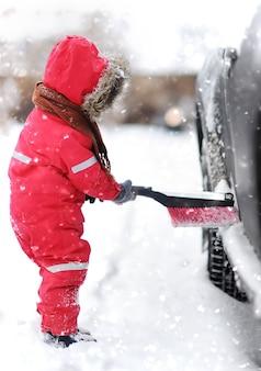 Lindo niño pequeño ayudando a cepillar la nieve de un auto