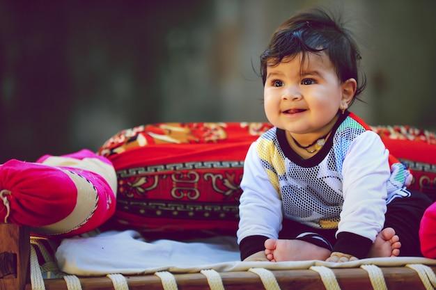 Lindo niño pequeño indio jugando en la cama de madera