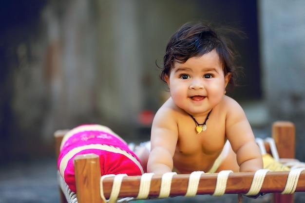 Lindo niño pequeño indio sonríe y juega en la cama de madera