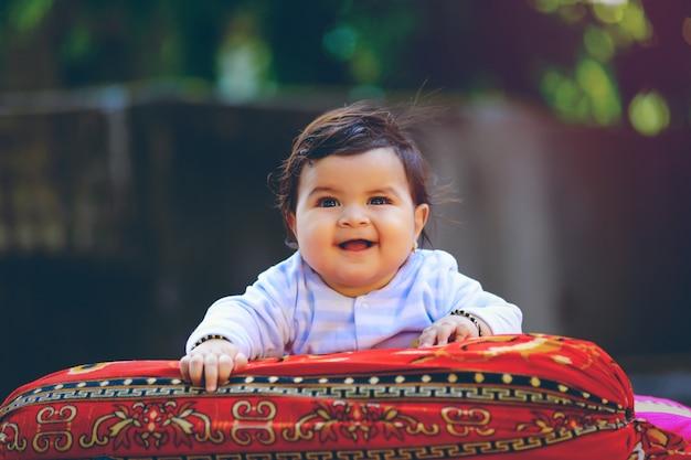 Lindo niño pequeño indio sonriendo y jugando delante de la casa