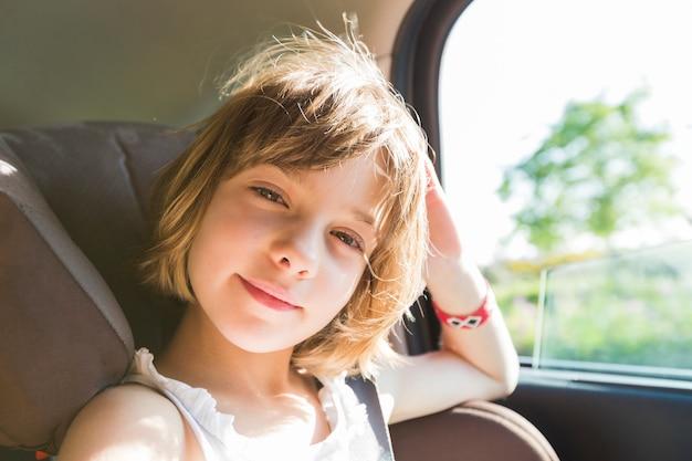 Lindo niño pequeño, niña rubia, en el asiento del automóvil con cinturones de seguridad feliz va a ir en el camino de la carretera, reflejo del sol reflejado