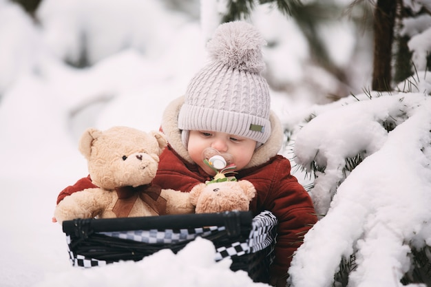 Lindo niño pequeño con ositos de peluche en bosque de invierno
