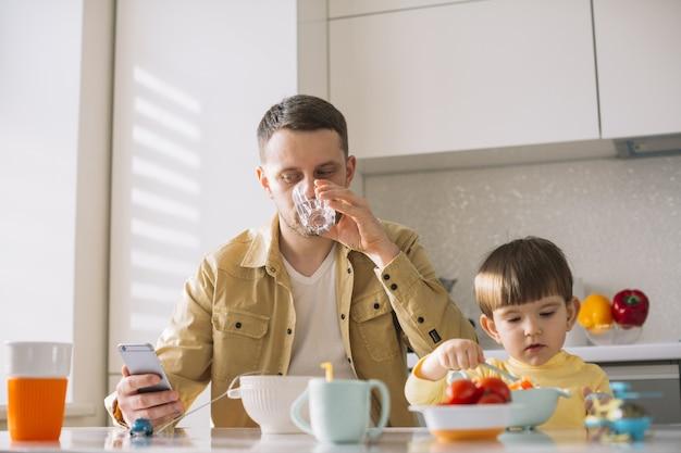 Lindo niño pequeño y su padre desayunando
