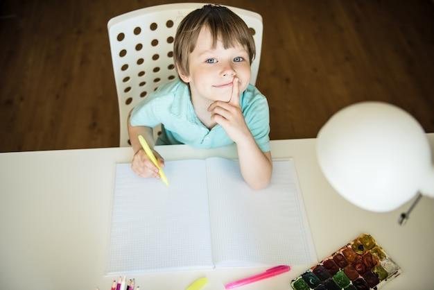 Lindo niño pintando con lápices de colores en casa, en el jardín de infancia o preescolar