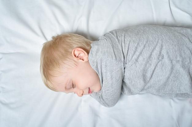 Lindo niño rubio durmiendo con su mano debajo de la cabeza.