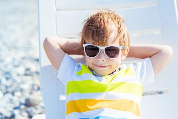 Lindo niño rubio con gafas de sol se sienta en una tumbona en la costa del océano