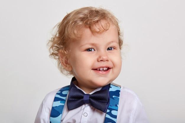 Lindo niño rubio con pajarita y tirantes de camuflaje azul, mirando directamente a la cámara con una gran sonrisa