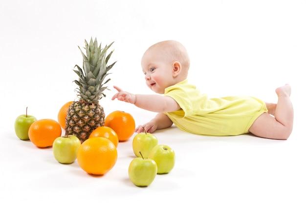 Lindo niño sano sonriente se encuentra sobre un fondo blanco entre frui