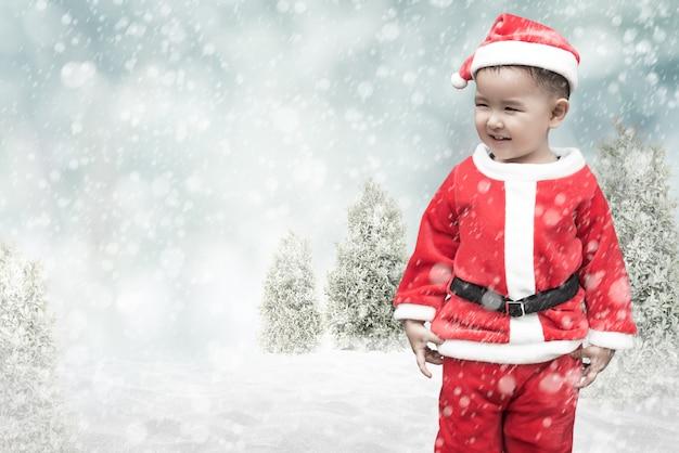 Lindo niño santa con nieve que cae