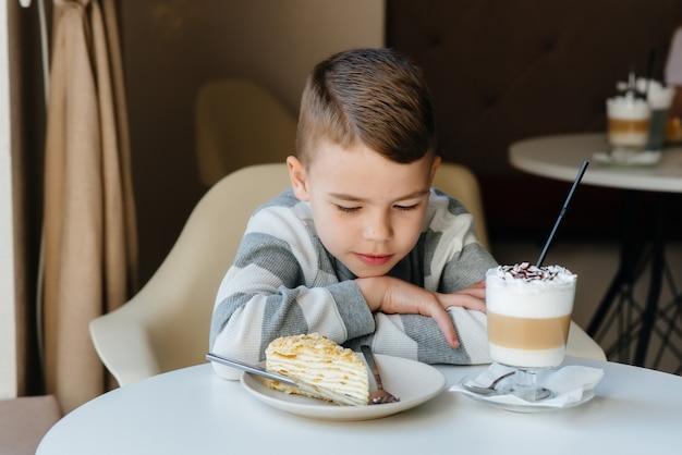Lindo niño está sentado en la cafetería y mirando pastel y coco