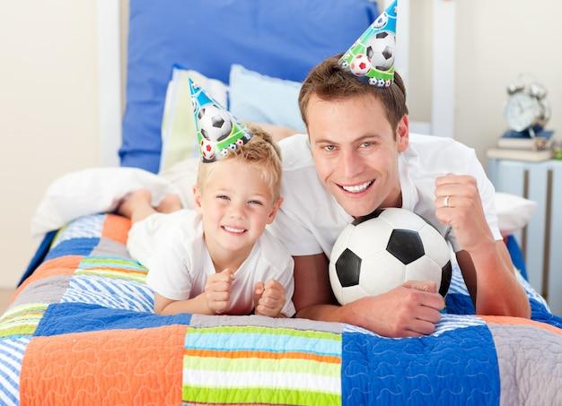 Lindo niño y su padre mirando un partido de fútbol