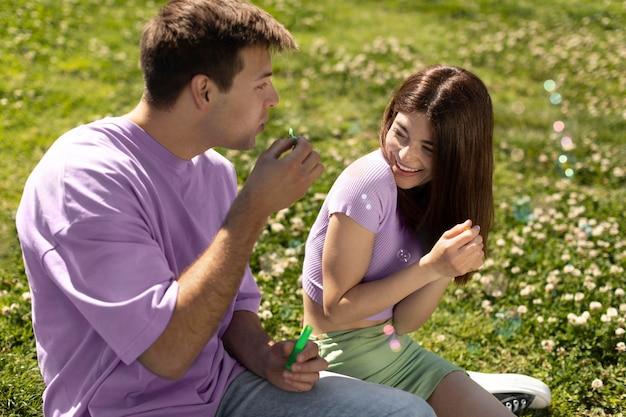 Lindo novio y novia jugando con pompas de jabón