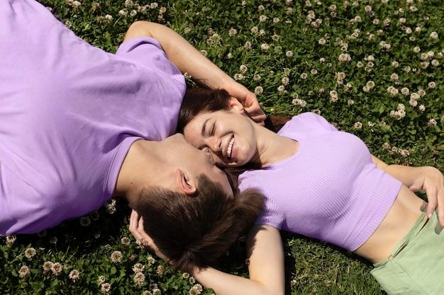 Lindo novio y novia tumbado en el césped