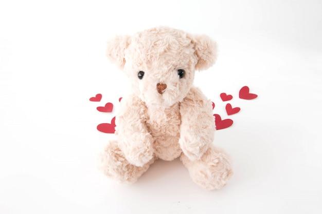 El lindo osito de peluche está muy feliz con muchos corazones en san valentín.