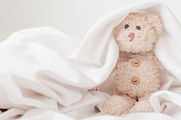 Lindo oso de peluche juega a las escondidas con tela, concepto happy feel.