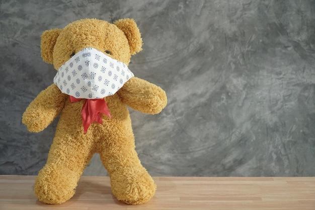 Lindo oso de peluche con mascarilla de tela de algodón en el piso de madera