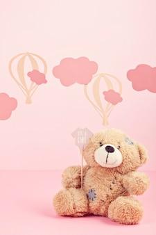 Lindo oso de peluche sobre el fondo rosa pastel con nubes y globos