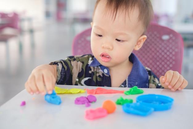 Lindo pequeño asiático 18 meses de edad niño bebé niño niño divirtiéndose jugando plastilina de colores / juego dought en el juego escuela / guardería, juguetes educativos para niños juego creativo para niños pequeños concepto