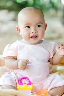 Lindo pequeño bebé asiático sentado y jugar con felicidad seleccionar foco poca profundidad de campo