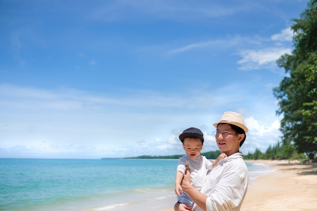Lindo pequeño niño asiático de 1 año / 18 meses de edad, niño, niño, juego con papá en la playa de arena blanca