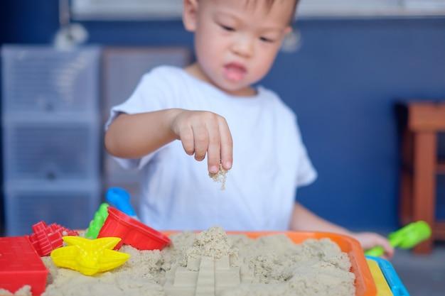 Un lindo y pequeño niño asiático de 2 años jugando con arena cinética en casa