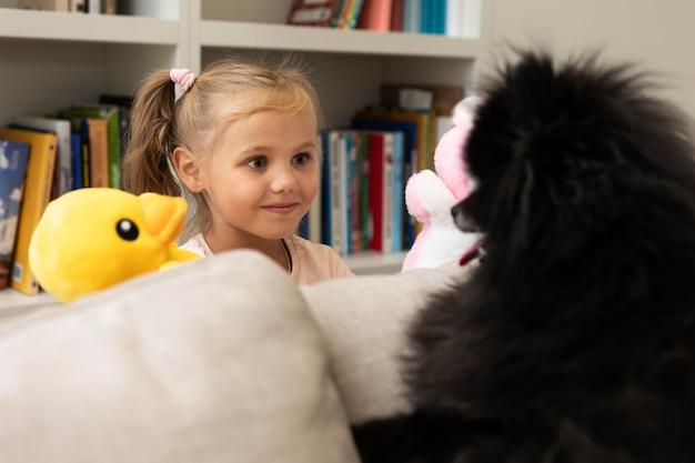 Lindo perro mirando a una niña con una marioneta de pato