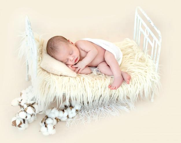 Lindo recién nacido acostado en la cama del niño