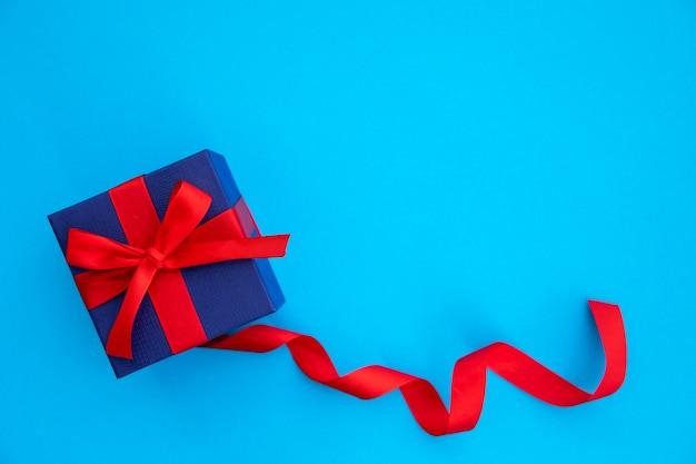 Lindo regalo azul y rojo con cinta.