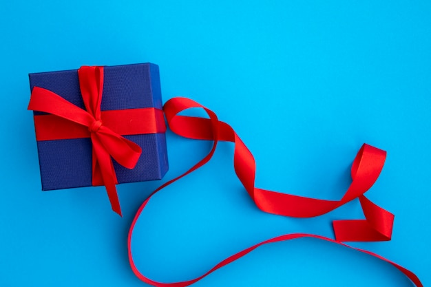 Lindo regalo azul y rojo con cintas.