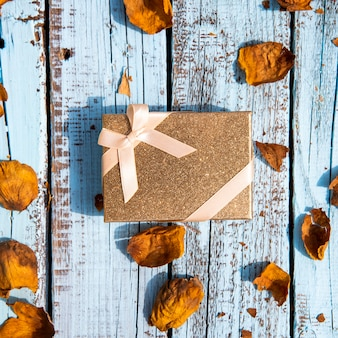 Lindo regalo rodeado de hojas secas.