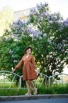 Lindo retrato de una niña con un sombrero marrón sobre un fondo lila en un jardín botánico. el pelo largo y rubio yace sobre los hombros.