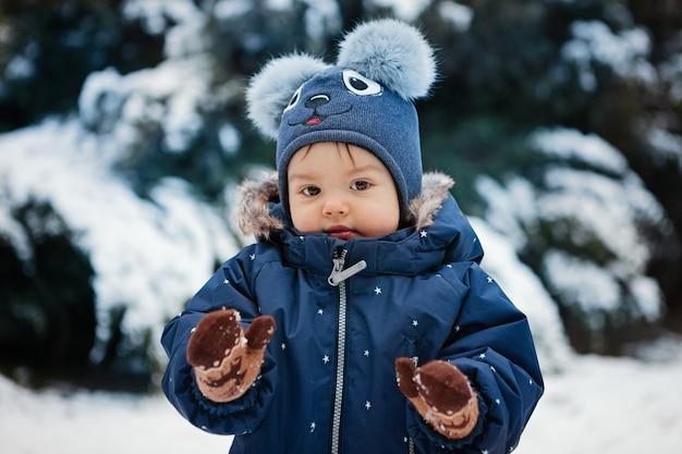 Lindo retrato de un niño pequeño en la nieve