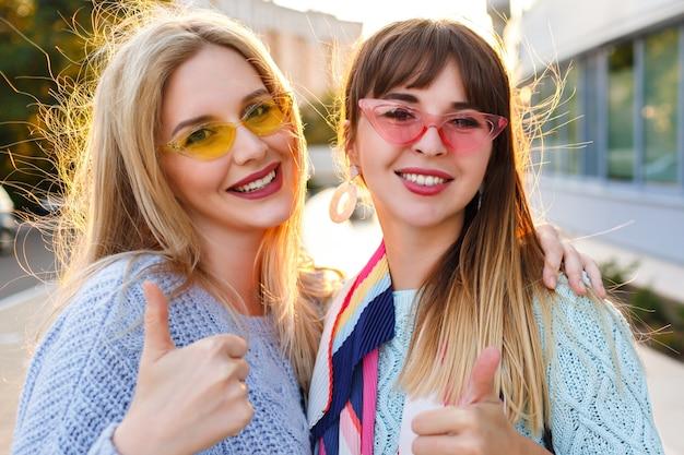 Lindo retrato soleado de cerca de dos magníficas damas muy elegantes sonriendo, vistiendo suéteres y gafas vintage, otoño primavera, metas de amistad.