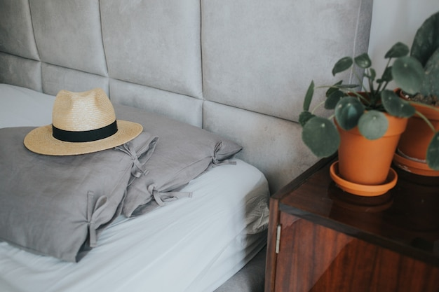 Lindo sombrero fedora en una acogedora cama con almohadas